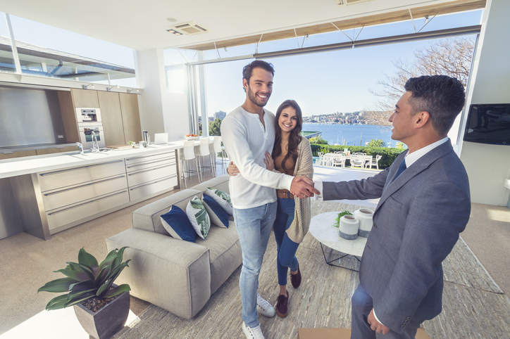 happy couple closing a deal with their real estate agent
